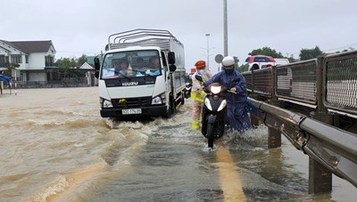 Quảng Nam: CSGT đưa người qua Quốc lộ 1A trong mưa lũ