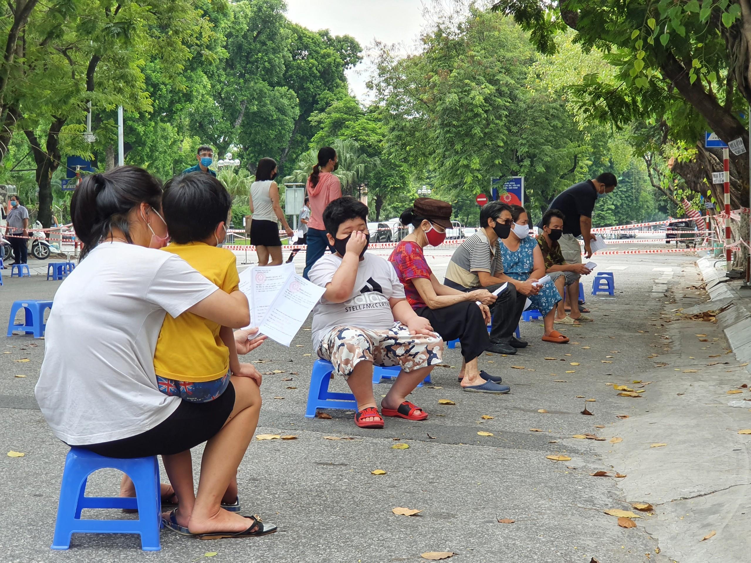 Sau khi điền phiếu, người dân sẽ được hướng dẫn ngồi chờ đúng theo giãn cách.