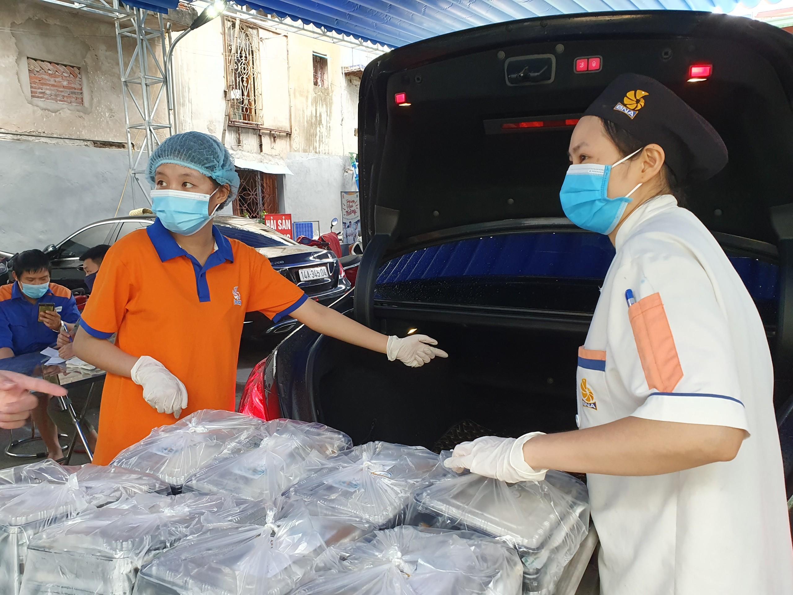 Đội ngũ tình nguyện viên cẩn thận xếp từng suất ăn lên xe để vận chuyển.