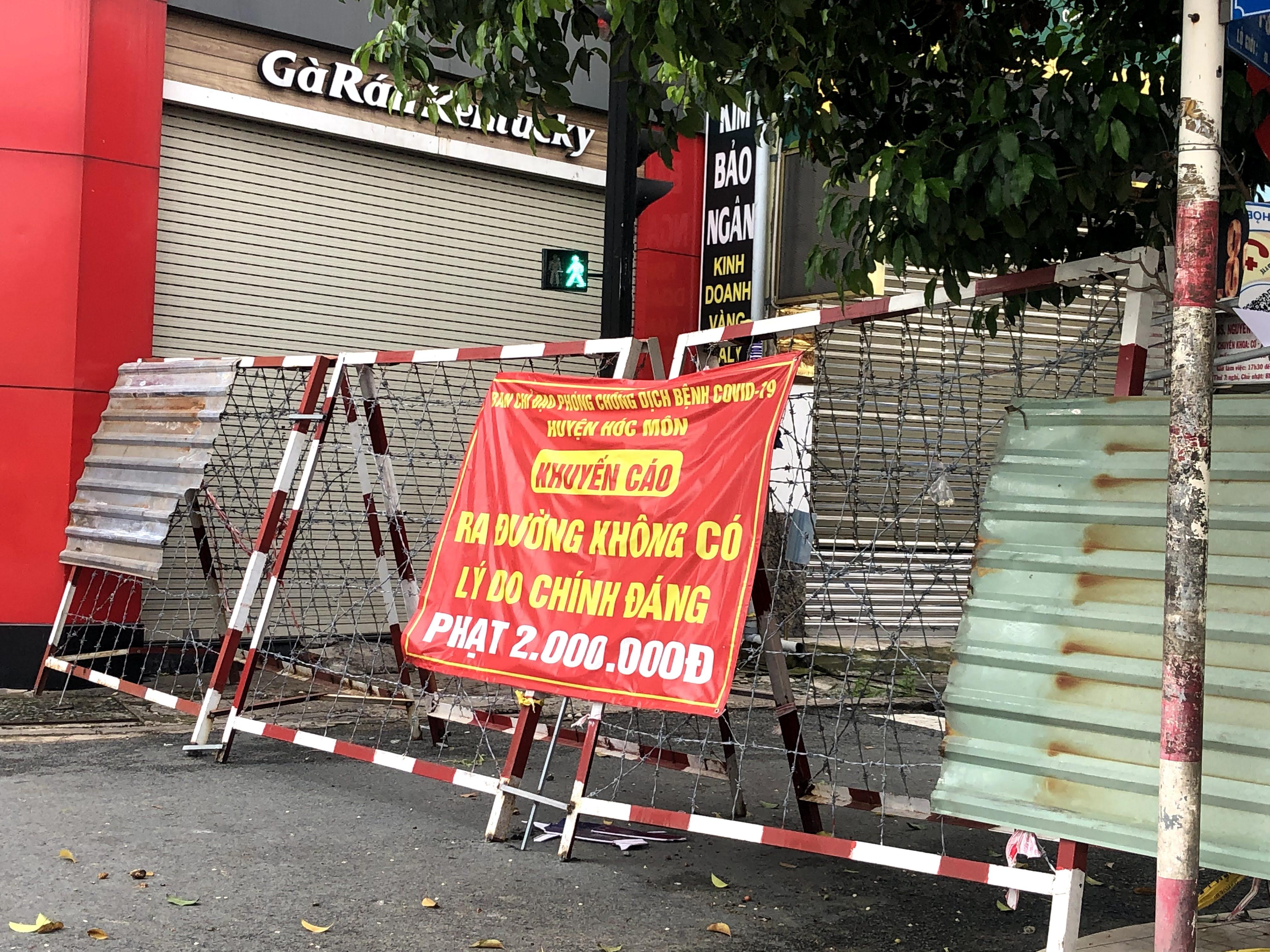 Chốt chặn một tuyến đường ở thị trấn Hóc Môn. Dù tín hiệu đèn đường vẫn hoạt động nhưng nhiều tháng qua không có bất cứ phương tiện nào có thể di chuyển được.