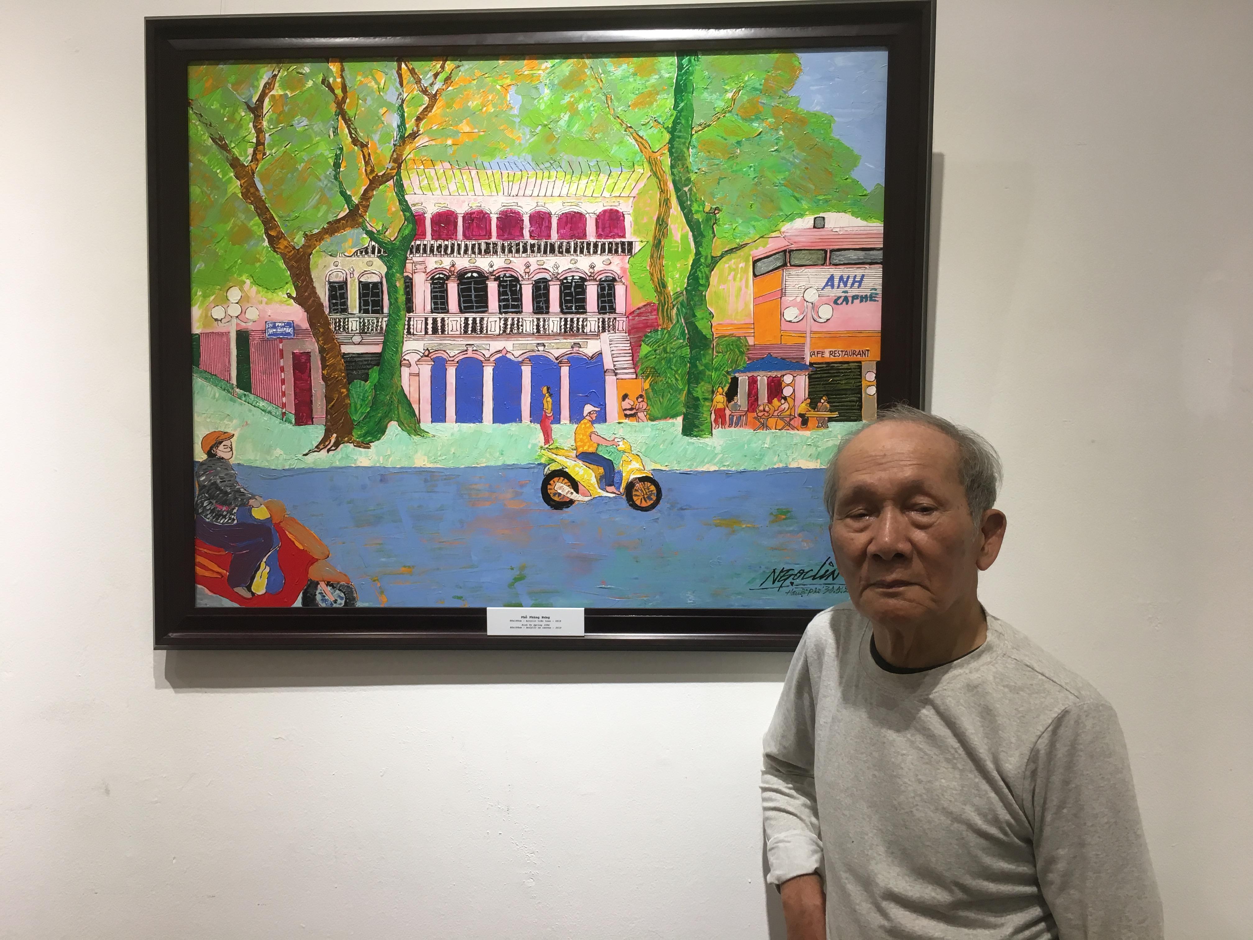 Họa sĩ Ngọc Linh bên một tác phẩm của mình tại triển lãm.