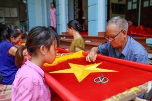 Gia đình ba thế hệ thêu cờ Tổ quốc tất bật trước dịp Quốc khánh 2-9