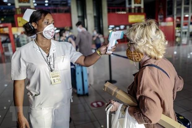 Nhân viên y tế Cuba kiểm tra thân nhiệt du khách nhằm ngăn ngừa dịch COVID-19 lây lan, tại một nhà khách ở Havana. (Ảnh: AFP/TTXVN).