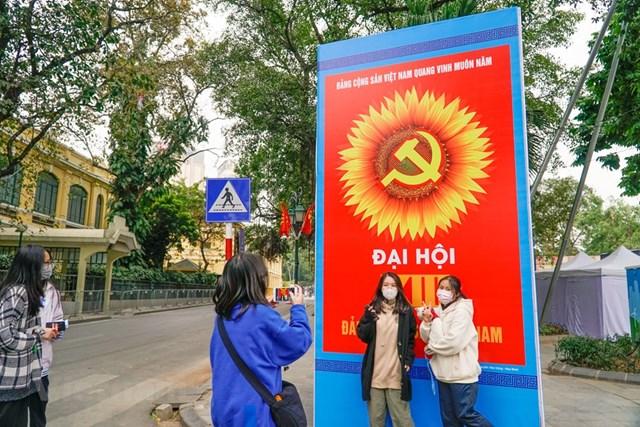 Các bạn trẻ thích thú chụp ảnh lưu lại kỷ niệm với tấm áp phích lớn. (Ảnh: Minh Hiếu/Vietnam+).