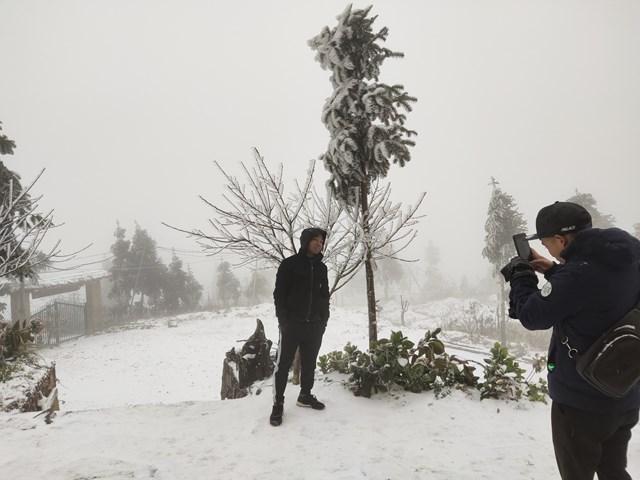 Khách du lịch chụp ảnh với băng tuyết ở Y Tý bên ngoài một homestay. Ảnh: Phu Suy Thó.