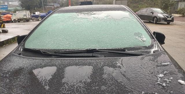 Mưa tuyết dần tan, băng giá phủ trên kính xe ô tô.