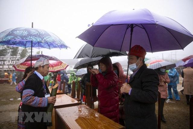 Thầy cúng mời du khách và các đại biểu tham dự lễ hội thưởng thức chút rượu trong ống nứa. (Ảnh: Trọng Đạt/TTXVN).