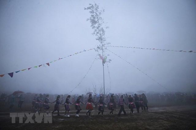 Các chàng trai, cô gái Mông cùng du khách nắm tay nhau nhảy múa theo tiếng khèn xung quanh cây nêu. (Ảnh: Trọng Đạt/TTXVN).