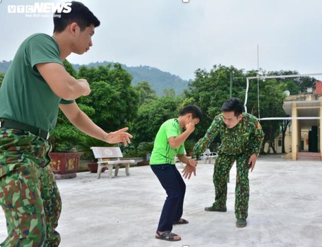 Thượng úy Nguyễn Huy Tiến dạy Tẩn Minh Khải bài võ thể dục của bộ đội biên phòng. (Ảnh: Quốc Việt).