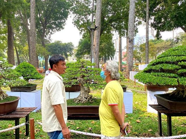 Nghệ nhân và du khách trao đổi kinh nghiệm chơi cây cảnh. Ảnh: Đại Việt.