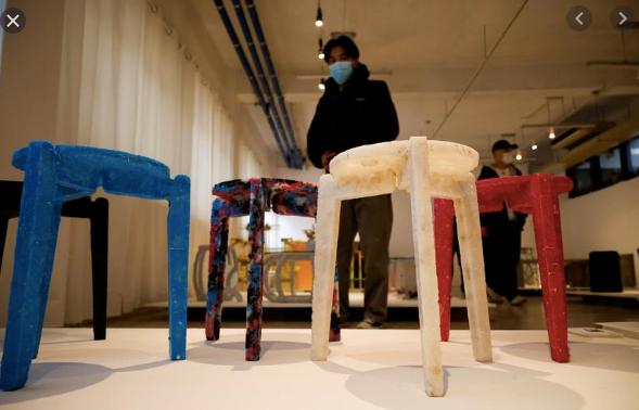 Nam sinh Kim Ha-neul với các ghế đẩu được làm từ khẩu trang đã qua sử dụng. Ảnh: Reuters.