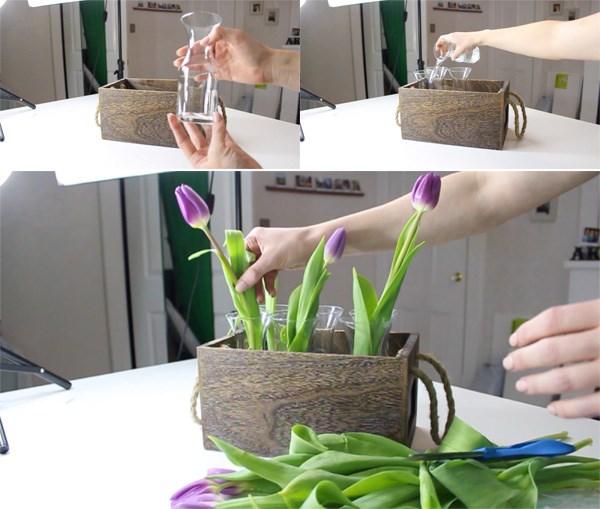 Bạn đặt 6 chiếc lọ thủy tinh vào trong khay gỗ, đổ nước ngập ½ chiếc lọ. Cắt các cành hoa tulip cắm vào trong lọ, mỗi lọ từ 1-2 cành, chiều cao của cành hoa tulip bằng hoặc cao hơn chiều cao của khay gỗ.