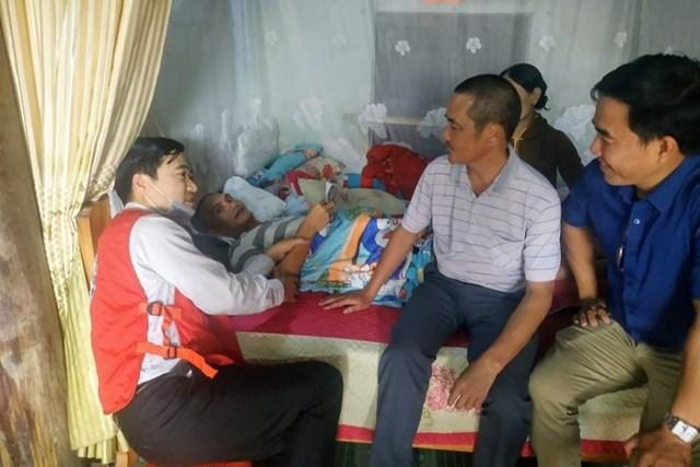 Thầy giáo Ngô Mậu Tình (áo đỏ) trong một lần trao hỗ trợ cho người có hoàn cảnh khó khăn, bệnh tật.