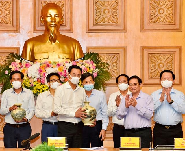 Thủ tướng Phạm Minh Chính trao quà tặng các cơ quan báo chí tại cuộc gặp mặt. Ảnh: VGP.