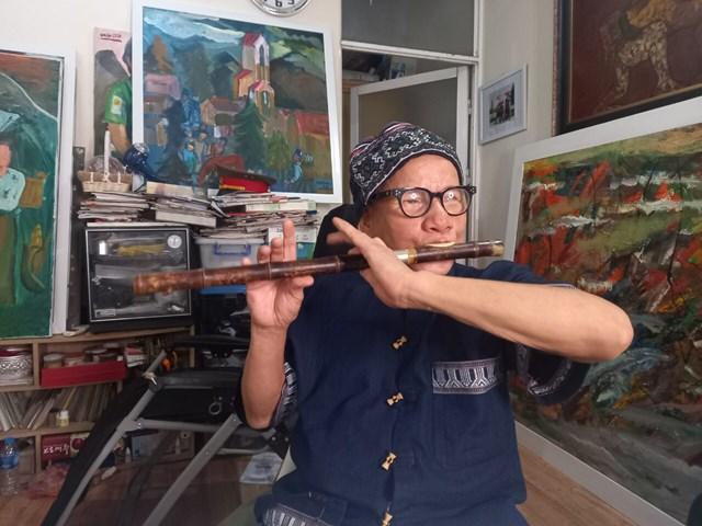 Họa sĩ Lê Duy Ứng tự học thổi sáo.
