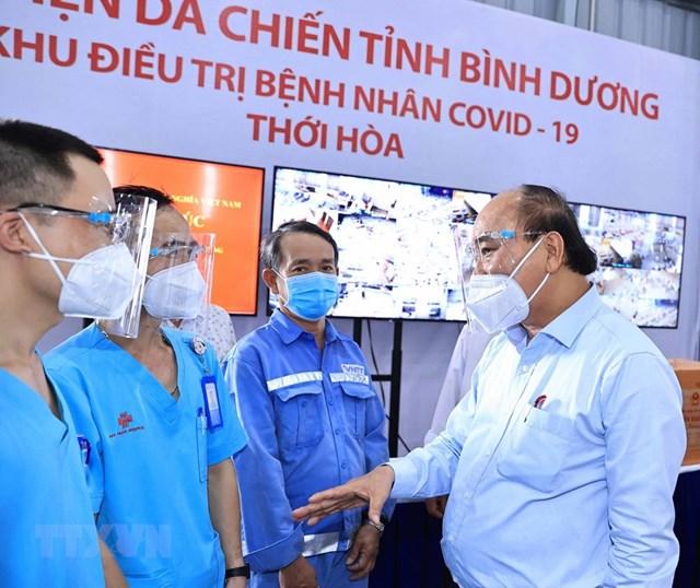 Chủ tịch nước Nguyễn Xuân Phúc thăm hỏi, động viên đội ngũ cán bộ, nhân viên y tế điều trị bệnh nhân Covid-19.(Ảnh: Thống Nhất/TTXVN).