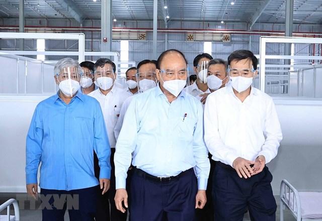 Chủ tịch nước Nguyễn Xuân Phúc, Chủ tịch UBTƯ MTTQ Việt Nam Đỗ Văn Chiến đến thăm Bệnh viện dã chiến tỉnh Bình Dương điều trị bệnh nhân Covid-19.(Ảnh: Thống Nhất/TTXVN).