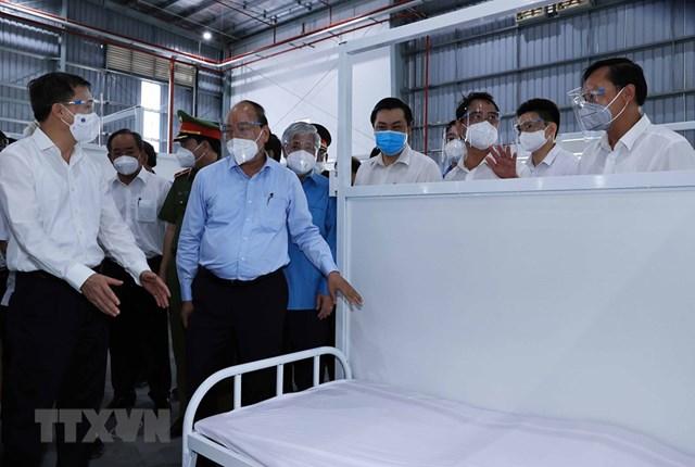 Chủ tịch nước Nguyễn Xuân Phúc, Chủ tịch UBTƯ MTTQ Việt Nam Đỗ Văn Chiến thăm bệnh viện. (Ảnh: Thống Nhất/TTXVN).