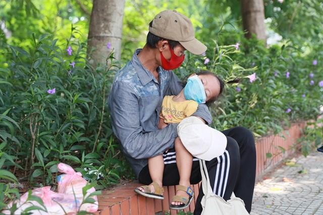 Hai bố con anh Chiến ngồi lặng lẽ trên vỉa hè, trong tay bố, em bé đang ngủ say.