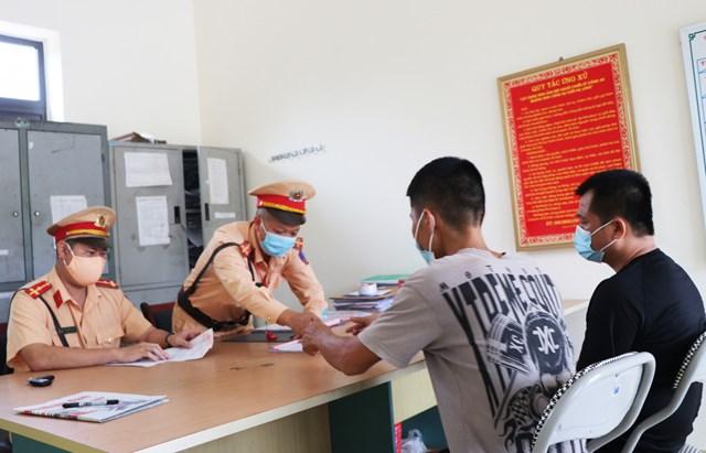 Lực lượng chức năng TP Uông Bí làm việc với 2 trường hợp Đinh Văn Huynh và Nguyễn Văn Trọng, không chấp hành các biện pháp phòng, chống dịch. Ảnh: QMG.