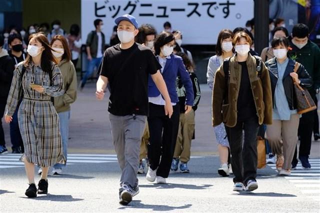 Người dân di chuyển trên phố ở Tokyo, Nhật Bản. (Ảnh: AFP/TTXVN).