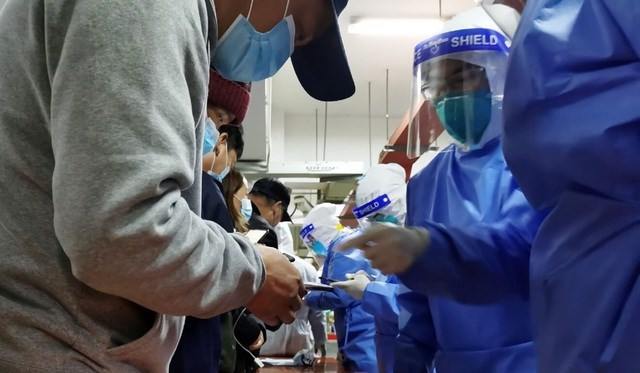 Nhân viên sân bay Phố Đông được các nhân viên y tế xét nghiệm Covid-19 hôm 22/11 (Ảnh: Weibo).