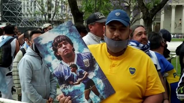 Một người hâm mộ rước ảnh của Maradona hòa vào dòng người tiễn biệt ông.