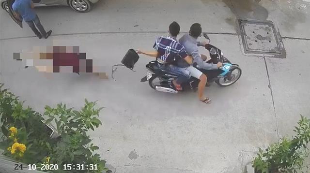 Hai nghi phạm đi xe máy cướp giật túi xách khiến nạn nhân té ngã xuống đường - Ảnh camera ghi lại.