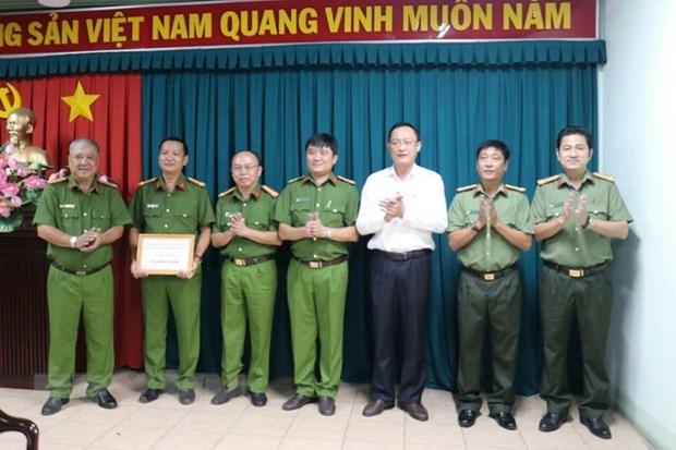 Đại tá Trần Văn Chính trao thưởng nóng 10 triệu đồng cho Công an thị xã Bến Cát. (ẢNh: TTXVN phát).