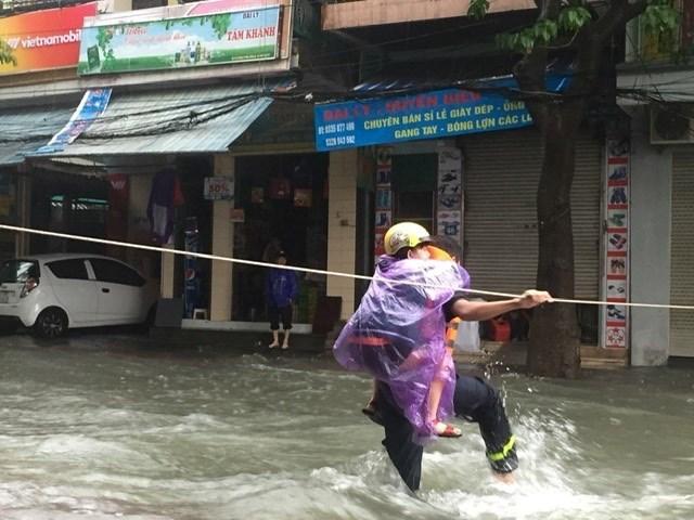 Nghệ An: Cảnh sát căng dây giữa dòng lũ, cứu sống 2 mẹ con đang co ro trên nóc tủ - 1