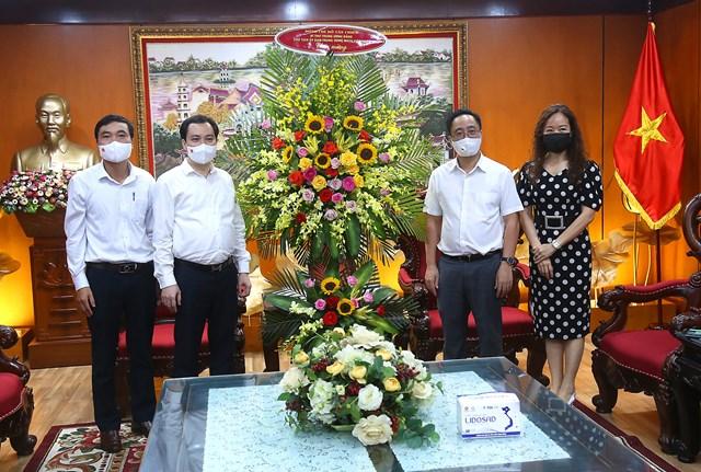 Ông Vũ Văn Tiếntặng hoa chúc mừng Đài Tiếng nói Việt Nam. Ảnh: Kỳ Anh.