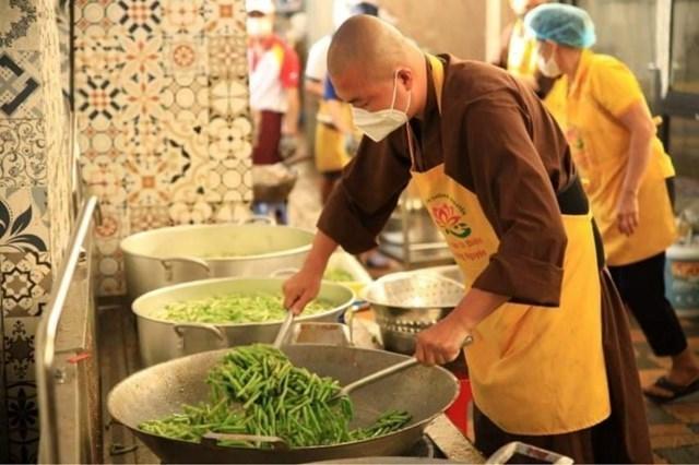 """Thầy Thích Minh Phú, Chủ nhiệm và chịu trách nhiệm chính tại """"Bếp ăn từ thiện Tường Nguyên""""đang chế biến những phần cơm đong đầy yêu thương gửi tặng tới các y bác sỹ ở bệnh viện dã chiến, những người nghèo ở khu cách ly, điều trị."""
