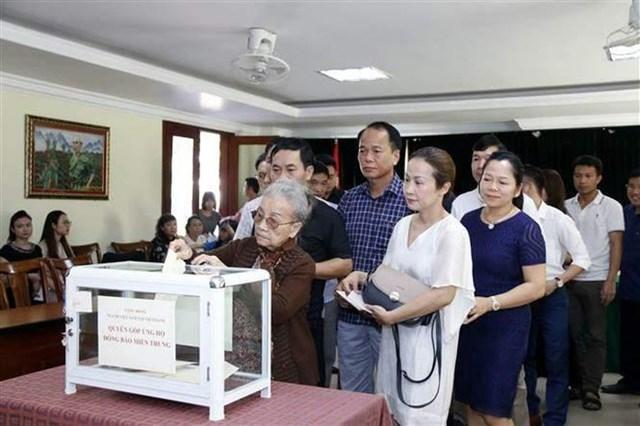 Cộng đồng người Việt Nam đang làm ăn sinh sống tại thủ đô Viêng Chăn đã thăm gia quyên góp, ủng hộ đồng bào miền Trung bị ảnh hưởng bởi bão lụt. Ảnh: Phạm Kiên/TTXVN.