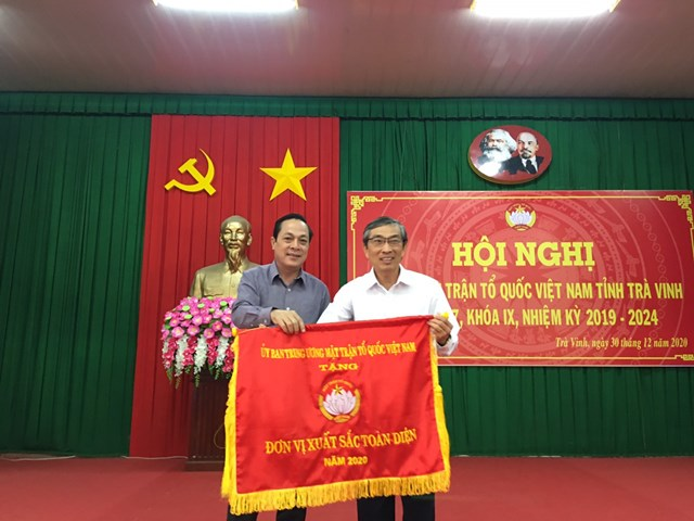 Ông Lâm Minh Đằng trao Cờ xuất sắc toàn diện năm 2020 của UBTƯ MTTQ Việt Nam cho Mặt trận Trà Vinh.