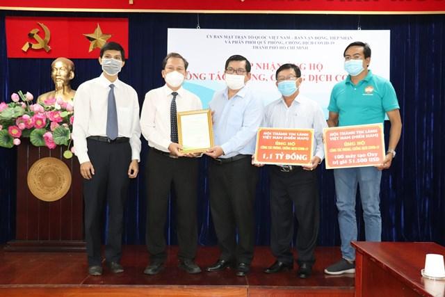 Mục sư Phan Vĩnh Cự (thứ 2, từ trái qua) trao bảng tượng trưng ủng hộ công tác phòng, chống dịch Covid-19 Thành phố.