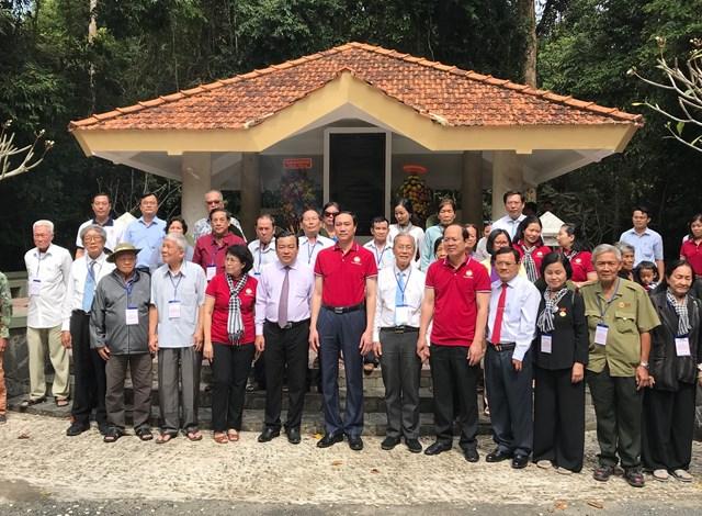Các vị lãnh đạo chụp ảnh lưu niệm cùng các đại biểu tại Di tích Căn cứ Mặt trận dân tộc giải phóng miền Nam Việt Nam.
