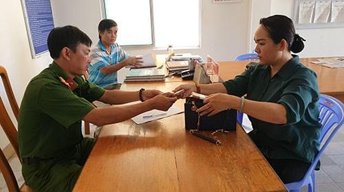 ChịTrần Thị Minh Trúc giao số tiền nhặt được cho cơ quan Công an phường Hưng Long, TP Phan Thiết.