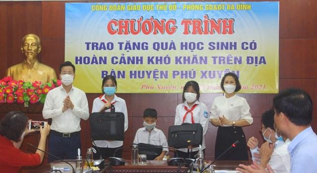Trưởng phòng GDĐT quận Ba Đình Lê Đức Thuận (bên trái ngoài cùng) trao tặng máy tính cho học sinh khó khăn huyện Phú Xuyên.