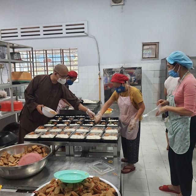Đại đức Thích Minh Đạo cùng các đầu bếp cho cơm và thức ăn vào hộp. Ảnh: Phương Chi.