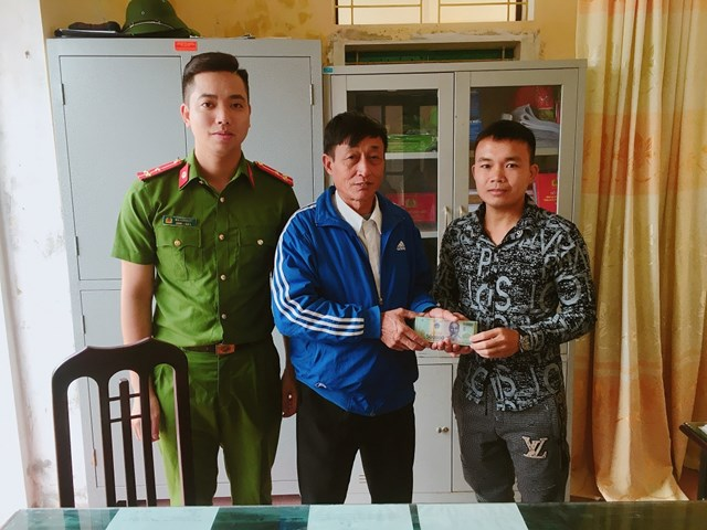 Anh Phú (bên phải) trao lại số tiền 38 triệu đồng cho ông Hỗ trước sự chứng kiến của Công an địa phương.
