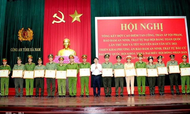 Chủ tịch UBND tỉnh Hà Nam Trương Quốc Huy (đứng giữa) trao thưởng cho các tập thể, cá nhân thuộc lực lượng Công an tỉnh.