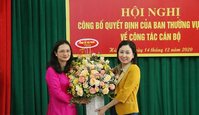 Phó Bí thư Thường trực Tỉnh ủy Hà Nam Đinh Thị Lụa (bên phải) trao quyết định điều động công tác cho bà Trần Thị Ngân.