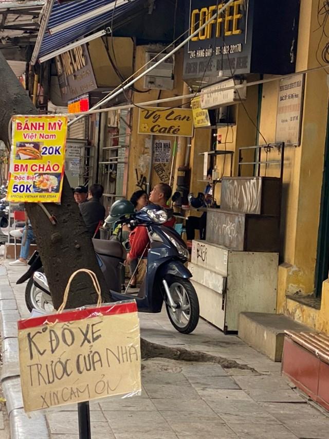Một số quán cafe nhỏ trên phố cổ vẫn bày bán ghế bên ngoài, người ngồi không đeo khẩu trang. Ảnh: L.A..