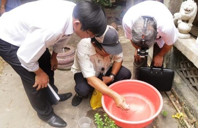 Cán bộ CDC Quảng Nam hướng đẫn người dân cách khử trùng nước nhiễm khuẩn.