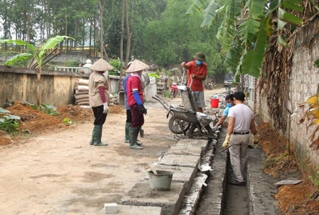 Người dân thôn Hữu Bằng, xã Tam Hợp, huyện Bình Xuyên tham gia cải tạo, xây dựng hệ thống cống, rãnh thoát nước thải ở khu dân cư. Ảnh: Nguyễn Hoan.