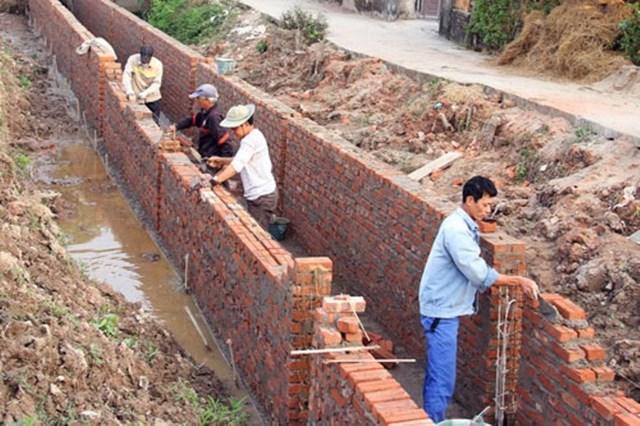 Người dân tham gia xây dựng hệ thống tưới tiêu tại xóm 1, xã Đồn Xá, huyện Bình Lục. Ảnh: Nguyễn Yến.