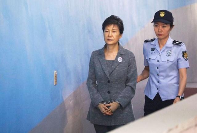 Cựu Tổng thống Hàn Quốc Park Geun-hye (trái) được áp giải đến phiên tòa ở Seoul năm 2017. Ảnh: Reuters.