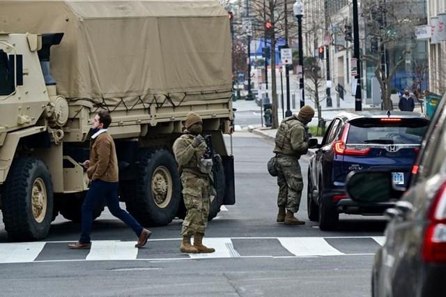 Các thành viên của Lực lượng Vệ binh Quốc gia kiểm tra giấy tờ tùy thân của những lái xe muốn đi vào đường cấm tại một trạm kiểm soát an ninh gần Nhà Trắng, ngày 15/1.