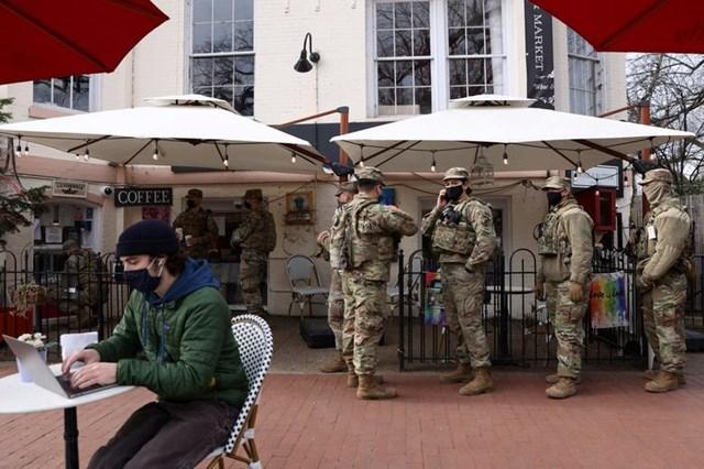 Các thành viên của Lực lượng Vệ binh Quốc gia xếp hàng chờ uống cà phê trong khi nghỉ giải lao.