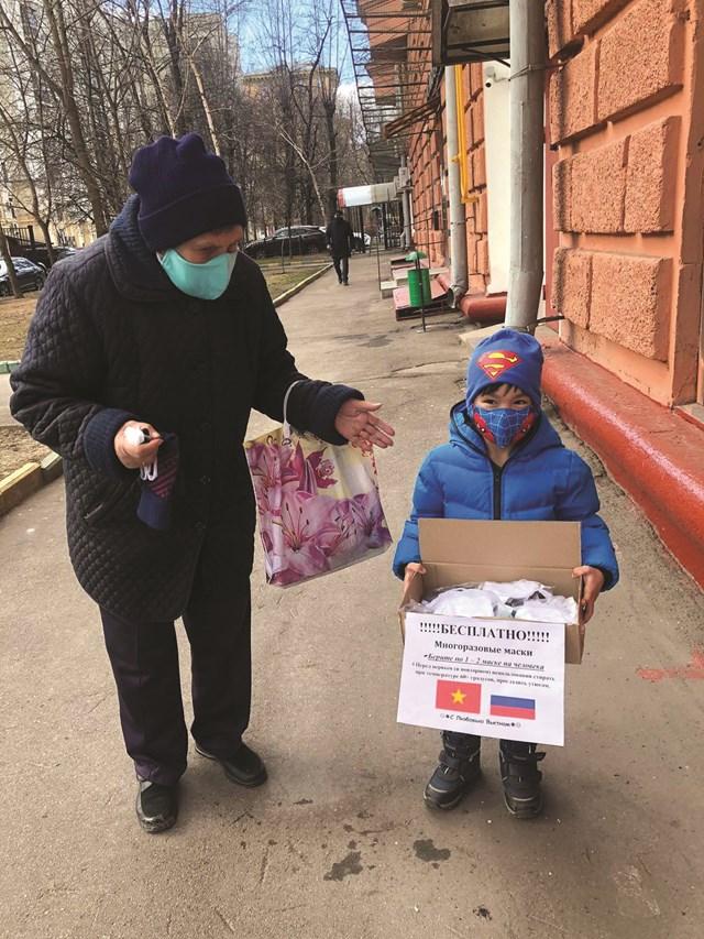 Em bé người Việt với thùng khẩu trang tặng người dân Nga.